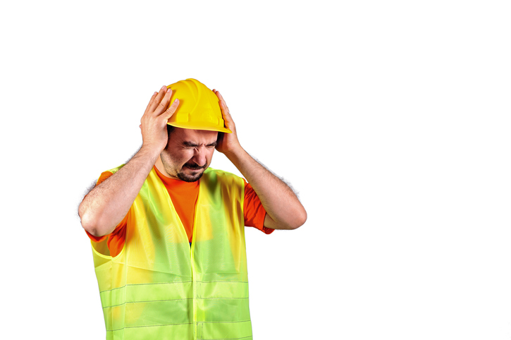 Manuel worker protecting himself from noisy environment isolated on white