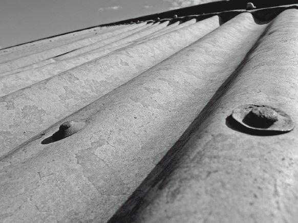 Dettaglio del fissaggio, in corrispondenza del colmo delle ondulazioni, di una lastra in una copertura in lastre ondulate di acciaio zincato