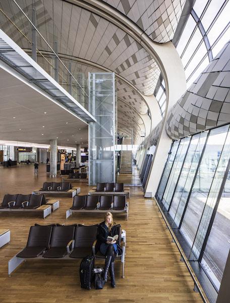 Il nuovo terminal su due piani ospita gates nazionali e internazionali sotto una copertura curva che mantiene l'espressione nordica e la semplicità razionale della struttura esistente © NORDIC Office of Architecture/Ivan Brodery