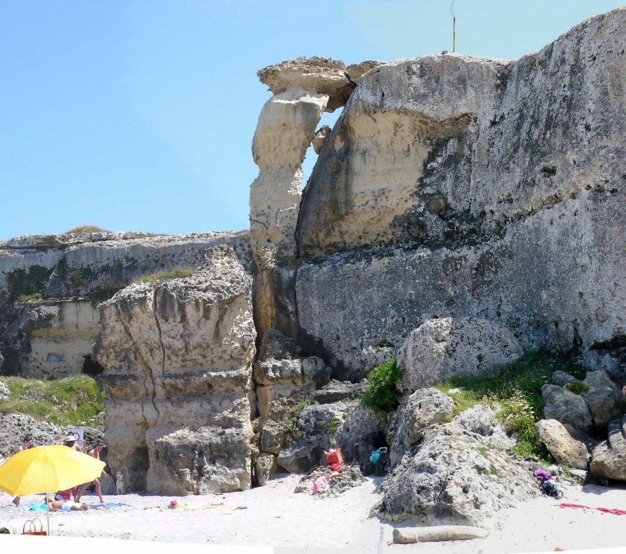 Fig. 6 Frequentazione umana al piede di una falesia con evidenti segni di pericolosità, malgrado un segnale (parzialmente coperto, sulla sinistra) di interdizione alla frequentazione (Torre dell'Orso, Lecce).