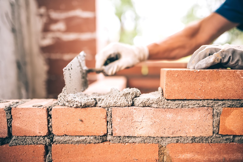 Bricklayer worker installing brick masonry on exterior wall