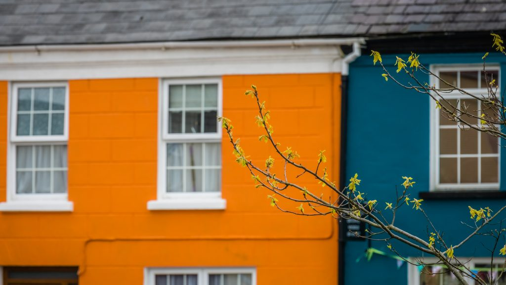 Orange and blue home facades in a small picturesque irish town Sneem on the Ring of Kerry route, Ireland
