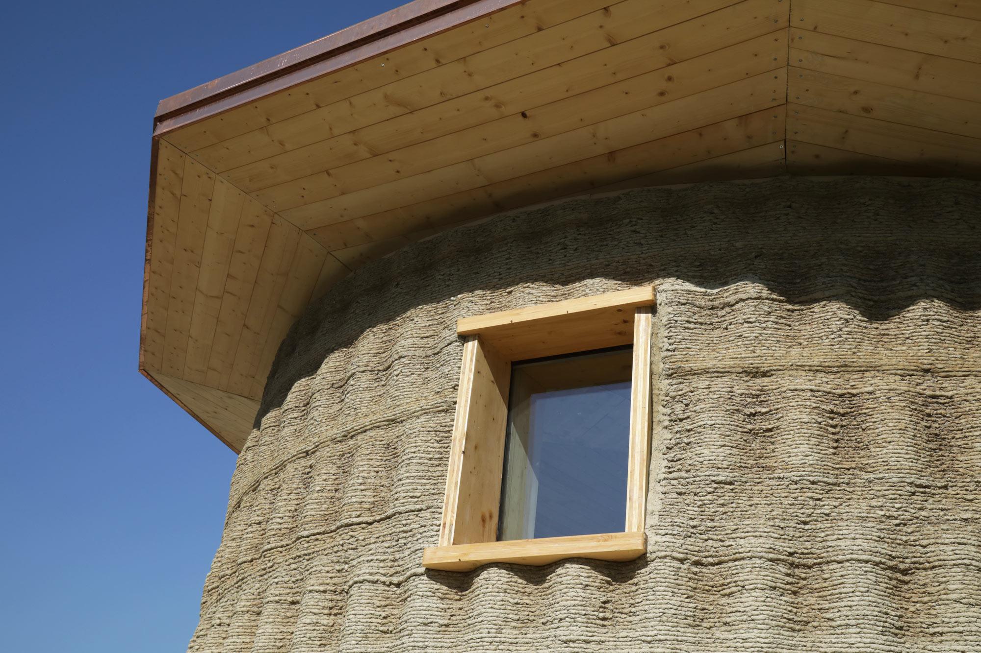 Dettaglio della parete monolitica stampata in 3D con materiali di scarto e a km0: terra cruda, paglia, lolla di riso e calce