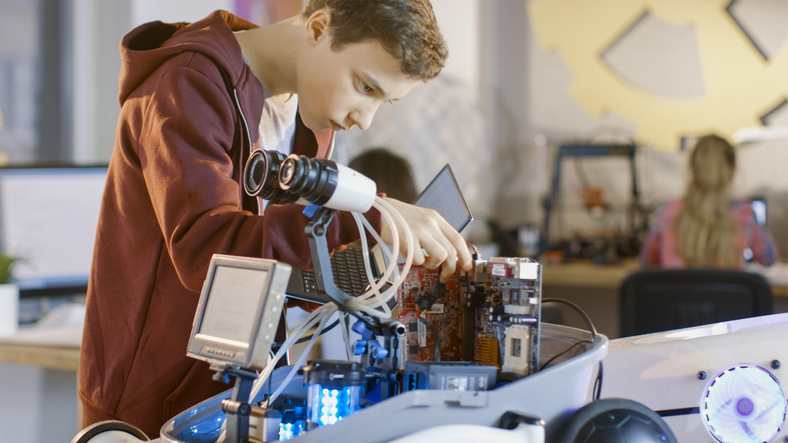 Boy Works on a Fully Functional Programable Robot with Bright LED Lights for His School Robotics Club Project.